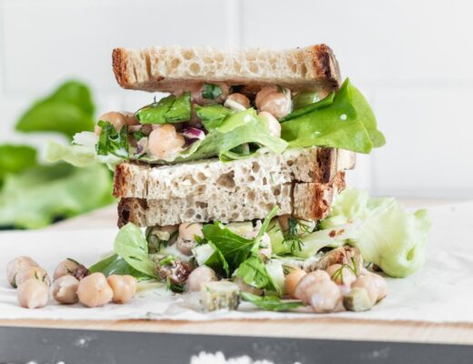 Chickpea Salad Sandwich with bread and lettuce sliced in half to show the inside on a wooden cutting board with a white backdrop