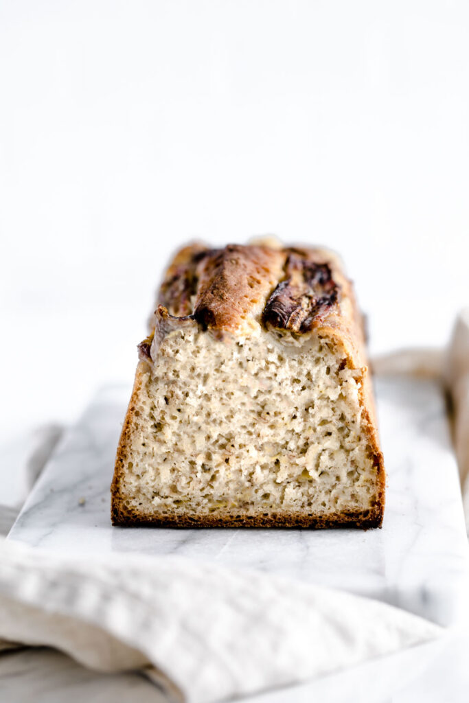 side view of sliced loaf of banana bread on white marble cutting board