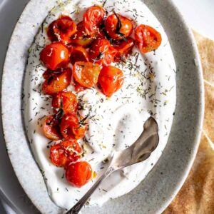 charred tomatoes on yogurt in an oval plate with a silver spoon and herbs on top and pieces of flat bread next to it