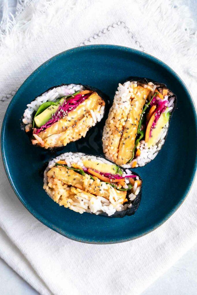 Three Onigirazu Rice Sushi Sandwiches on a white surface in a blue bowl
