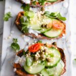 three sweet potato toast with toppings on a marble white backdrop