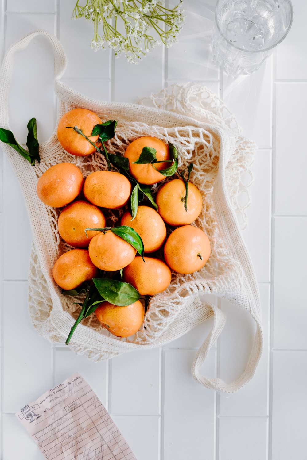 an open cotton shopping bag with mandarins and green leaves on a marble table