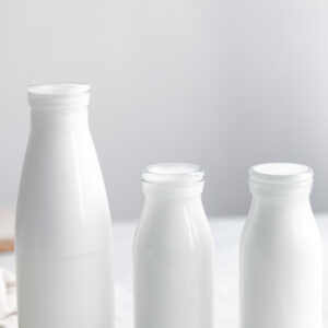 three different size glass bottles with coconut milk with white background