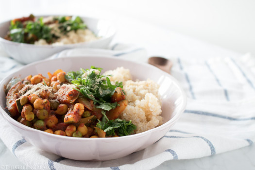 Chickpeas and tomato sauce topped with herbs in a white bowl on a blue striped napkin with a wooden spoon