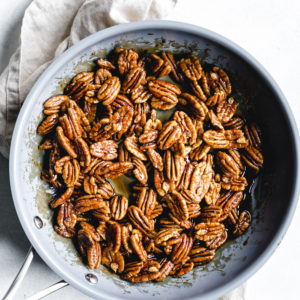sticky cooked candied pecans in blue skillet on a beige napkin
