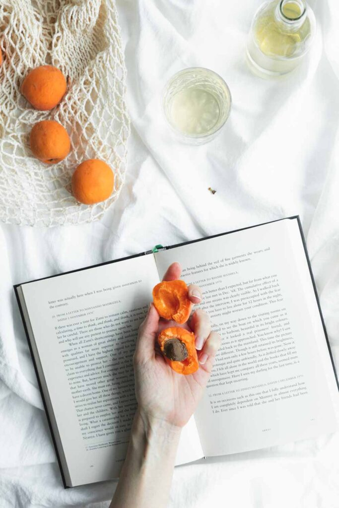 an open book with a hand on it with an open apricot in the hand on a white blanket with more apricots and drinks