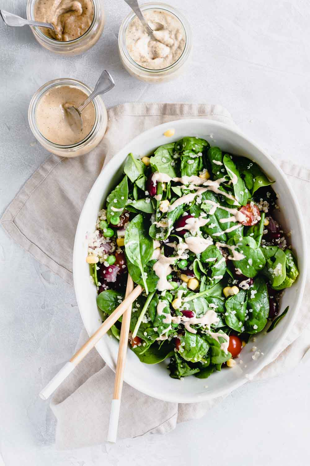Quinoa salad in oval bowl with chopstick on a lightbrown napkin and a light backdrop next to a small jar of dressing with a teaspoon.