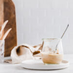 Spicy almond dressing in a small glass jar with a teaspoon on a light backdrop with a wooden cutting board, light brown napkin and wooden utensils in the background.