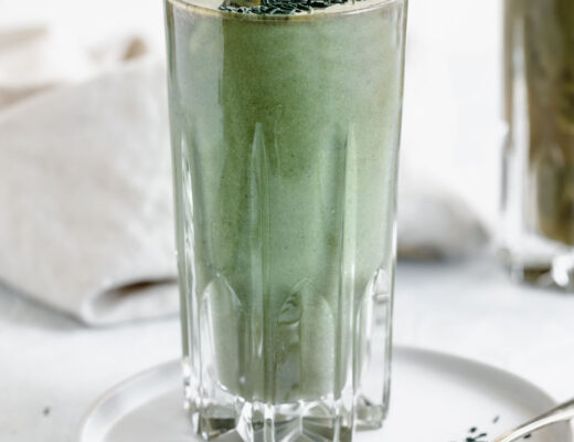 green smoothie in tall glass on white plate with a spoon with spirulina