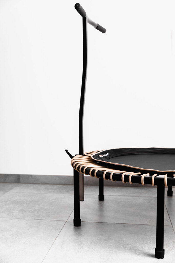 black bellicon rebounder with a stability bar on a grey floor with a white wall