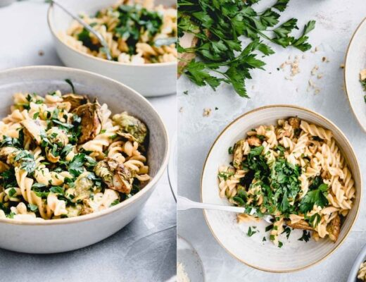 Two bowls with Brussels sprout pasta and chopped parsley on a white backdrop and a small edge of a pasta pan in the corner and fresh parsley on a wooden cutting board in the other corner