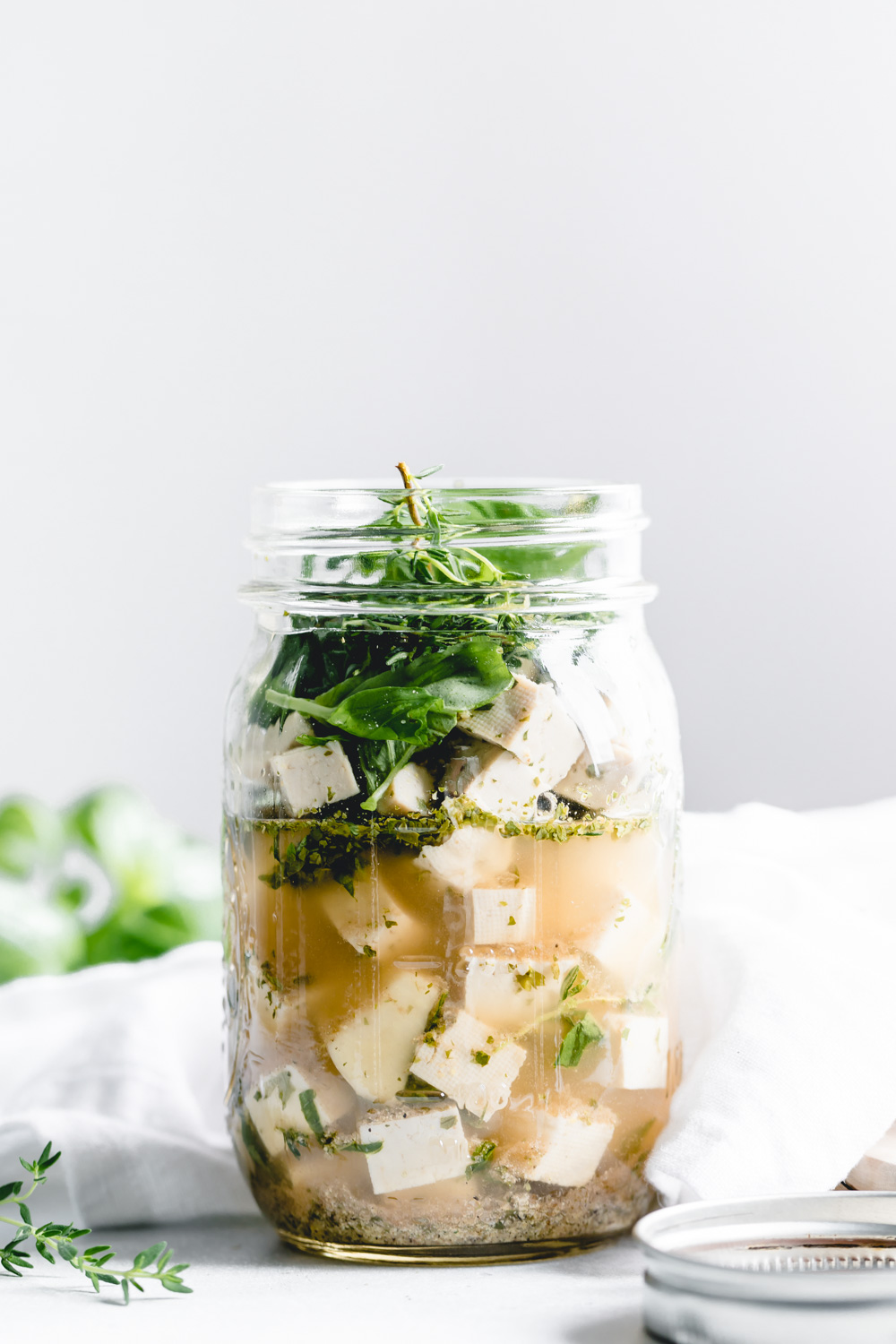 vegan feta cheese in glass jar with herbs with a white backdrop