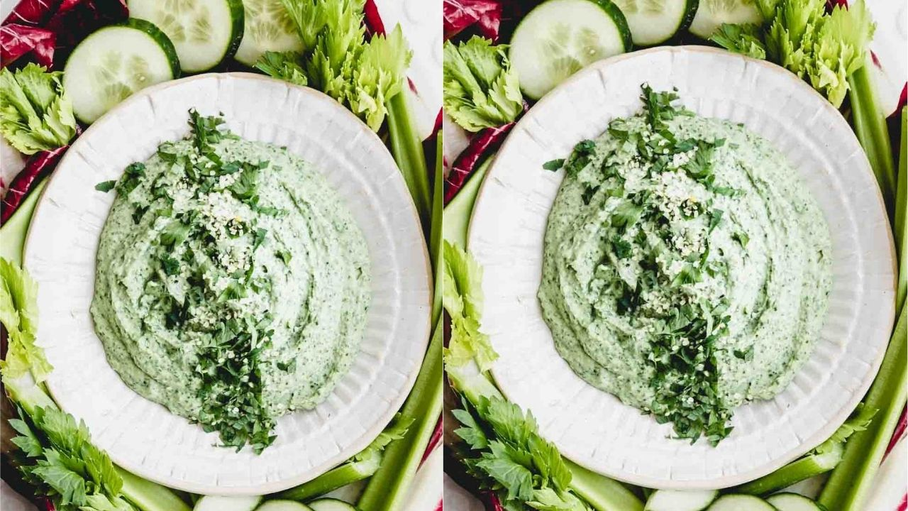 white bean dip in bowl with green herbs as topping on a backdrop of raw vegetables